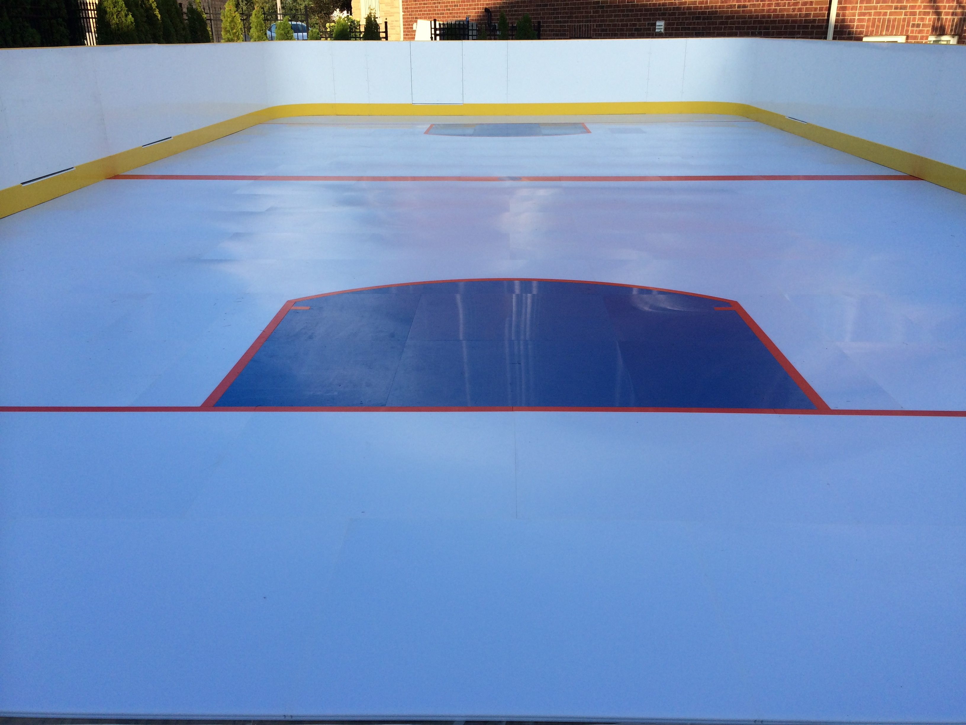 A synthetic backyard rink in Ontario, Canada with hockey boards