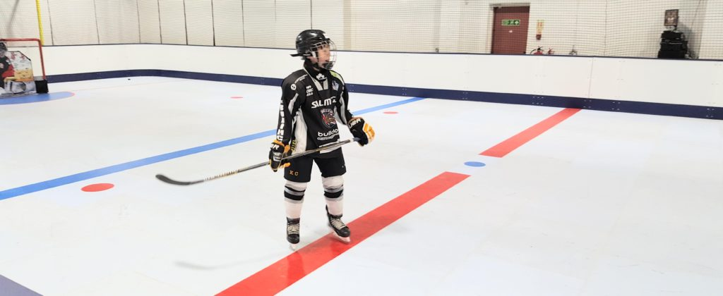 A young hockey player learning how to skate on synthetic ice at home.